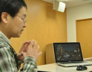 女川町の津波の写真を映し出しながら話をする佐藤紀生さん