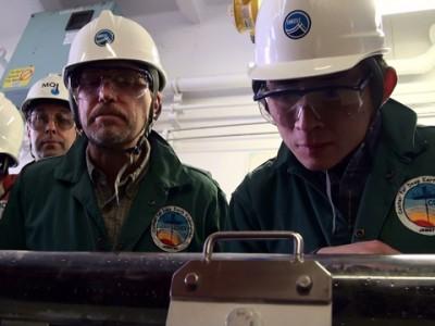「ちきゅう」での研究風景(右が氏家さん)。作業着にヘルメット姿は、フィールドでの調査ならでは。提供:海洋研究開発機構