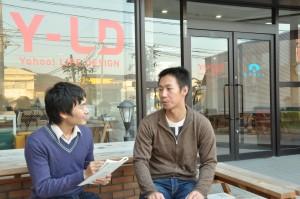 ヤフー石巻復興ベースの前で話をする石森洋史さん(右)