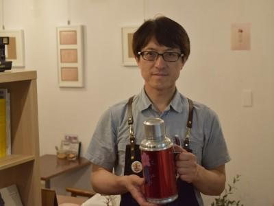 東京都新宿区、早稲田通り沿いにある「喫茶 タビビトの木」は旅をテーマにしたカフェ。尾林安政店長(47)がこれまでに訪れたタイやインド、チベットなどの料理を提供する。今年5月でオープンから1周年を迎えた。旅先で知らない人同士が集う「ゲストハウス」みたいな店にしたいという。日常の中で旅を感じられる場、そして人と人とが繋がれる場として、こだわりが詰まった店だ。  (トップの写真:中国で使われているティーポットを手にする尾林安政店長=2018年5月18日、新宿区西早稲田の喫茶タビビトの木、戸恒幾汰撮影)