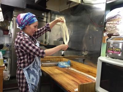 パティグリさんがラグメンを作っている。両手で引きのばして作って、茹で、鶏肉や羊肉、野菜、唐辛子などの炒めものをかけ、食前に混ぜて食べる。
