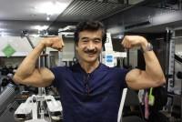 浮きたつ上腕二頭筋は、見る者を魅了する。国内のボディビル大会で数々の賞を獲得している横浜市在住の中島幸忠(なかじまゆきただ)さん(64)は、平日にはデイサービスの管理者としてお年寄りの方々に運動の指導を行っている。土曜日にはジムのトレーナーとして教室を開くなど、仕事の傍らハードなトレーニングを続けており、いかにしてその体を磨き上げているのか、それを支える原動力について聞いた  (トップの写真:デイサービス施設で上腕二頭筋を披露する中島幸忠さん=2019年6月7日、横浜市保土ヶ谷区釜台町、上野貴臣撮影)