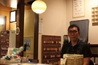 東京都新宿区大久保の一角にある万年湯は、2016年にリニューアルして以来、外国人や若い人でにぎわっているという。今、流行りの韓国のアメリカンドッグ「ハットグ」を片手に女子学生も訪れる。タオルを無料で貸し出しているので、手ぶらで行くことができる。訪ねてみると、浴室の障子風の大きな窓からは、柔らかな光が差し込み、いわゆる昔からの富士山が描かれた銭湯ではなく、壁には鶴のモザイクタイルがはめ込まれていてモダンな雰囲気だ。  (トップ写真:都心の隠れ湯を意識した「万年湯」を経営する武田信玄さん=2019年7月14日、東京都新宿区大久保、萩野愛撮影)